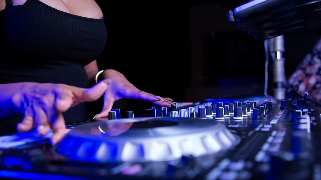A female DJ using turntables on a controller