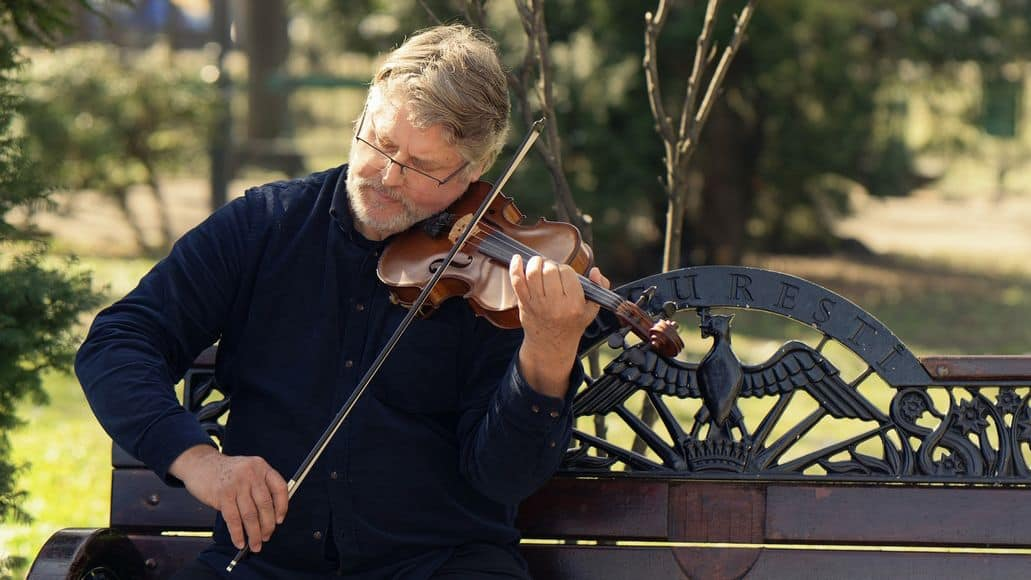 Violinist playing on park bench