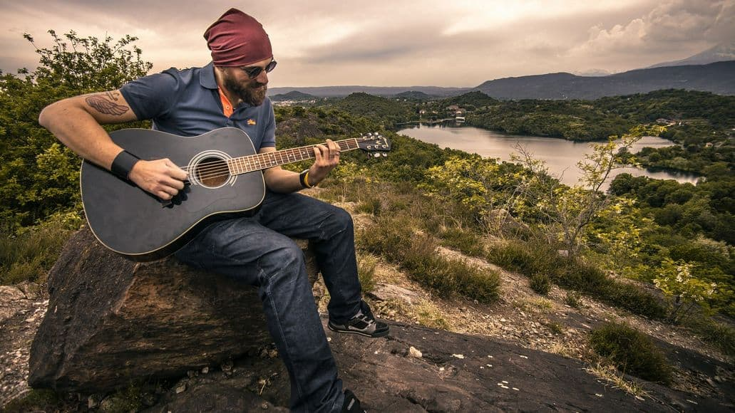 Amateur guitarist practicing in nature