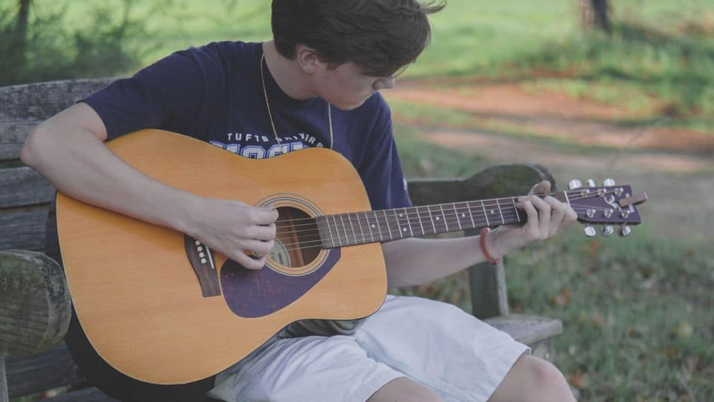 Boy practicing scales on guitar