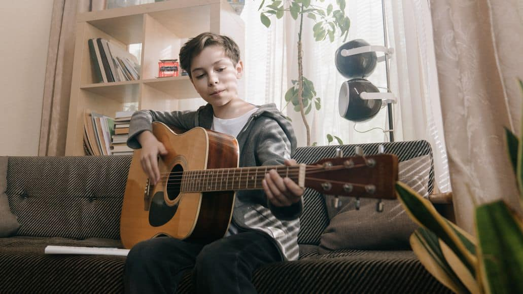 Child practicing hard on the guitar