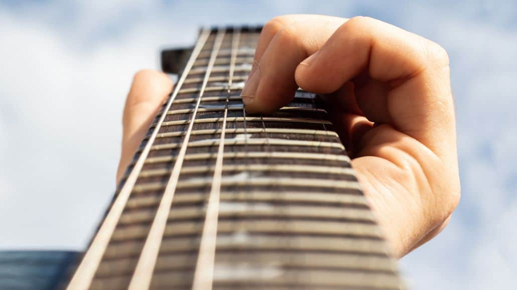 Guitarist fingering frets on fretboard